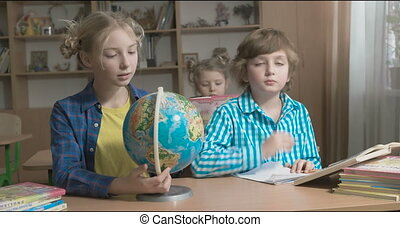 Children learning and doing homework in school classroom