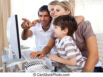 Children learning how to use a computer with their parents at home