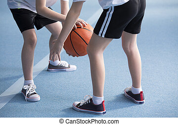 Children learning to dribble basketball - Close-up on young...