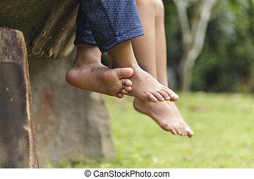 Children legs barefoot, Kids sitting dangling their feet in summer concept for family, friends