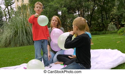 Children let their balloons fly away and one hits the camera...