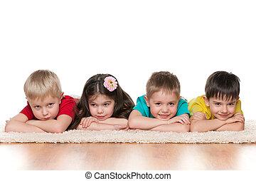 Children lie on the white carpet