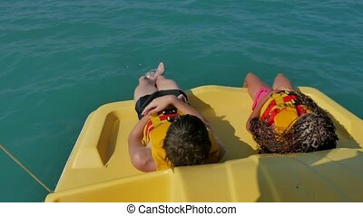 children lie resting on a yacht boat sea ocean. kids ride a catamaran boat in the ocean on the water