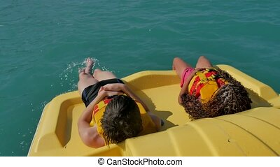 children lie resting on a yacht boat sea ocean. kids ride catamaran boat in the ocean on the water