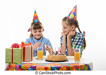 Children light a match to light candles on a cake on a holiday