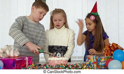 Children Lighting Candles at the Birthday Cake