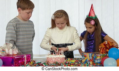 Children lighting candles on the birthday cake