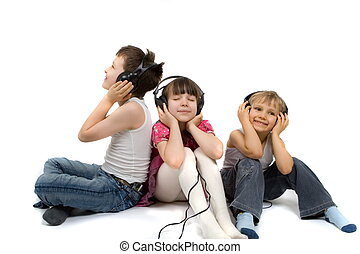 Young girl and her two brothers sitting together, listening to music on headphones. Taken in studio; isolated on white background.