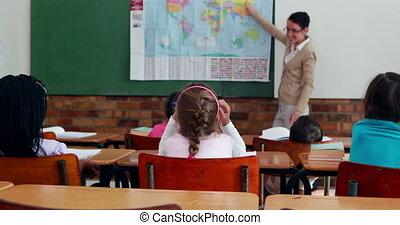 Little children listening to teacher showing the map in classroom in elementary school
