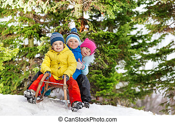 Children little boys and girl slide on sledge