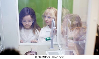 Children look at the spectacular chemical experiment with...