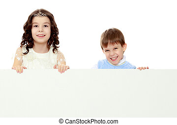 Children look out from behind the banner.