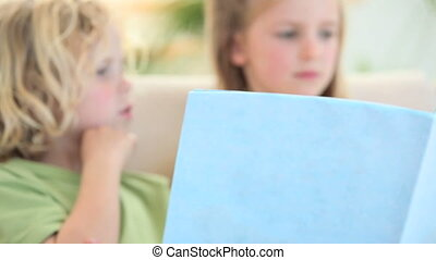 Children looking a book while sitting on a sofa