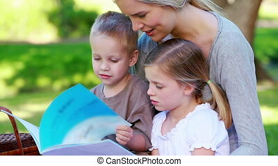 Children looking a picture book with their mother in a park