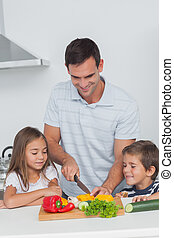 Children looking at their father who is cutting vegetables