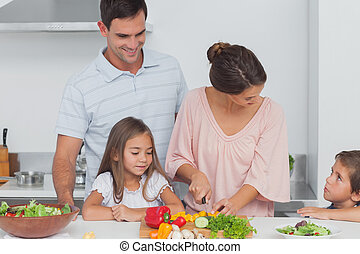 Children looking at their mother preparing vegetables