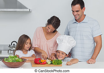 Children looking at their mother who is cutting vegetables