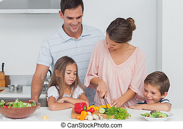 Children looking at their mother who is preparing vegetables