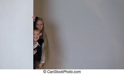 children looking out from behind white blank placard.