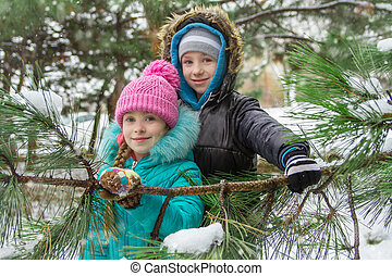 Children looking through snowy pin branches