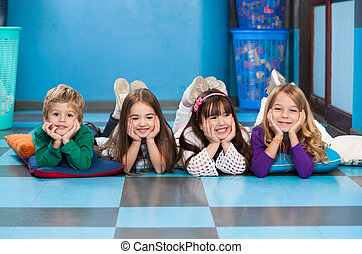 Portrait of cheerful children lying in a row on floor in classroom