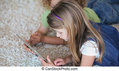 Children lying on the carpet a tablet and a laptop