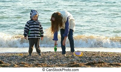 Children make a castle of sand on the beach. - Children make...
