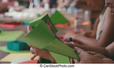 Children Make Crafts Out of Paper at the Table, Hand Made. ...
