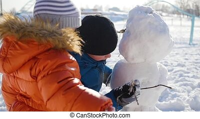 children making a snowman in the Playground - children...
