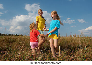 Children on a meadow - Girls wearing colorful t-shirts...