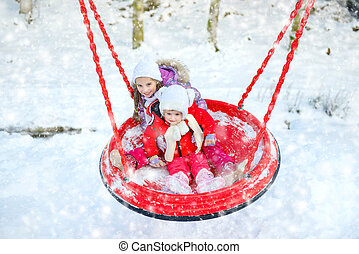 children on a swing in winter park