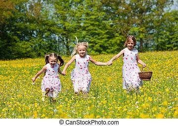 Children on Easter egg hunt with baskets - Children on an...