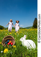 Children on Easter egg hunt with bunny - Children on an ...