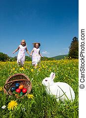 Children on Easter egg hunt with bunny - Children on an...
