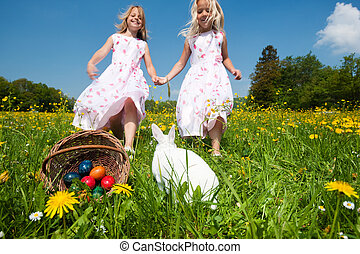 Children on Easter egg hunt with bunny - Children on an...