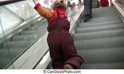 children on escalator in shop