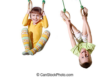 children on gym rings - two 4 year old kid hanging on...