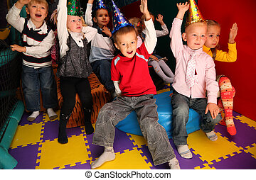 Children on holiday in kindergarten with raised hands
