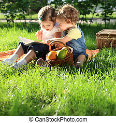 Children on picnic - Children reading the book on picnic in ...
