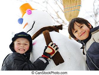 Children on snow with snowman