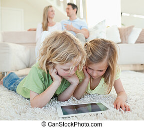 Children on the floor with tablet and parents behind them -...