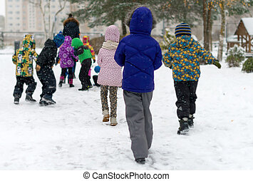 Children on walk in kindergarten in the winter.