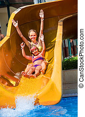 Children on water slide at aquapark. - Two children on water...