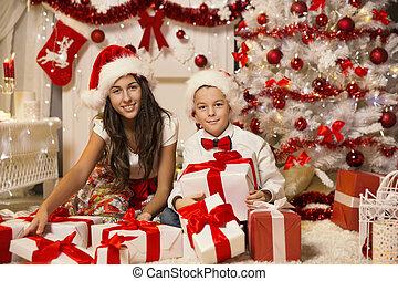 Children Opening Christmas Present Gift Box, Boy and Girl in Santa Hat Celebrating Xmas