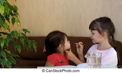 Children paint their faces with colors. The girl paints the face of another girl with paints. Blush on the cheeks. Behind the glass table.
