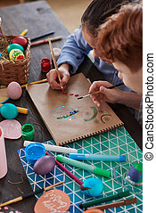 Children painting eggs at the table