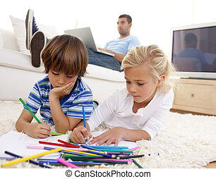 Children painting in living-room and father using a laptop ...