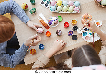 Children painting together at the table