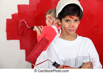 Children painting wall in red