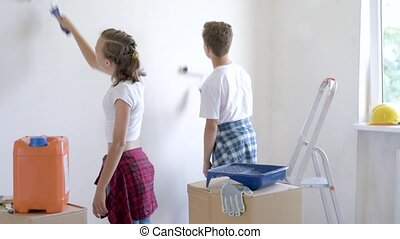 Children painting wall in room